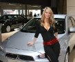 beatiful blonde next to a mitsubishi lancer