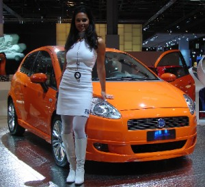 Sexy Girl standing next to an orange Fiat Punto
