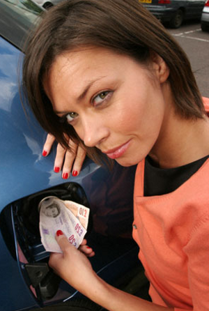 Sexy girl inserting bill notes into her blue car gas tank