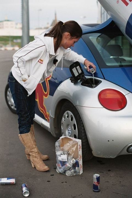 Babe filling a Volkswagen (VW) Beetle gas deposit with Red Bull cans