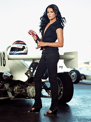 Beautiful Danica Patrick standing next to a racing car